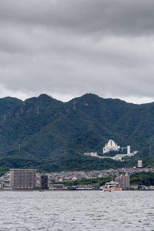 Hiroshima, Japan - September 20, 2016: Mori Art Museum with a view of the sea, is the large building in the mountains on the right. Seen from Miyajima Island across the Inland Sea.