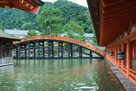 Hiroshima, Japan - September 20, 2016: Bridge and vermilion halls at itsukushima Shinto Shrine on Miyajima Island. Row of lanterns. Construction barely above sea level.