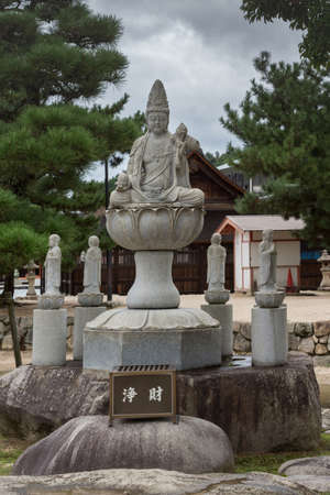 Hiroshima, Japan - September 20, 2016: Stone Quan Yin statue outside the Daiganji Buddhist Temple. She sits on a lotus and pedestal. Surrounded by small statues of Bodhisattvas. On Miyajima Island.
