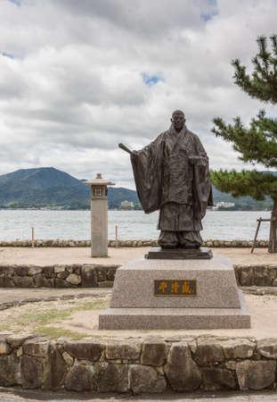 Hiroshima, Japan - September 20, 2016: Statue of Taira No Kiyomori, 12th century military leader, at the shore of Miyajima Island. He was the benefactor of the Itsukushima Shinto Shrine. Inland Sea in back.