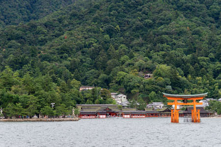 Hiroshima, Japan - September 20, 2016: Iconic vermilion Torii in front of Itsukushima Shinto Shrine set against the jungle top hill on Miyajima Island. Seen from on the Inland Sea.