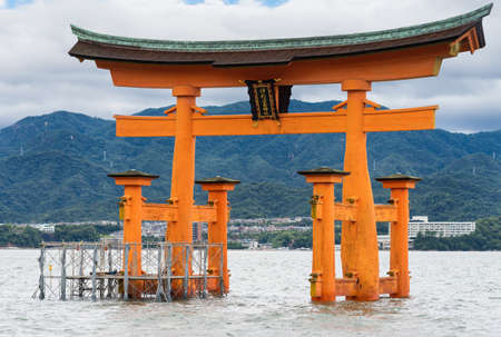 Hiroshima, Japan - September 20, 2016: Iconic historic vermilion Torii in front of Itsukushima Shinto Shrine stands in the water of the Inland Sea off Miyajima Island. Mainland jungle top hills in background.