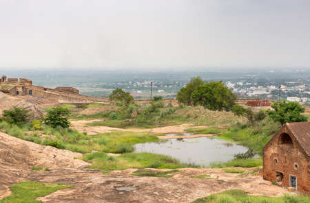 Dindigul, India - October 23, 2013: Rain water is collected in a couple of ponds inside the historic Dindigul Rock fort. View over wall onto surrounded region. Green environment around lake.