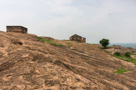 dispersed: Dindigul, India - October 23, 2013: Brown-beige boulder plain inside historic Dindigul Rock Fort. Two ruins and a tree dispersed in landscape. Light blue sky. Editorial