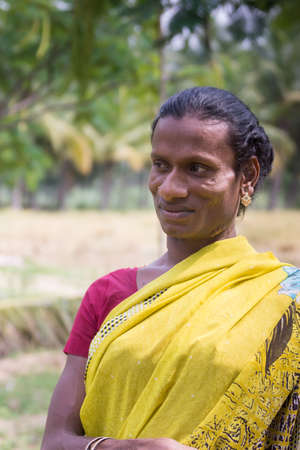 transexual: Dindigul, India - October 23, 2013: Smiling Hijra transgender person in a rural setting wears a beautiful yellow sari with maroon T-shirt. Her name is Sandra. Editorial