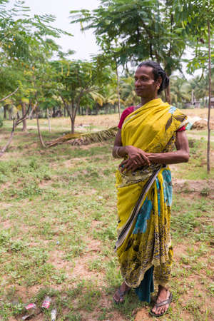 Dindigul, India - October 23, 2013: Hijra transgender person in a rural setting wears a beautiful yellow sari with maroon T-shirt.