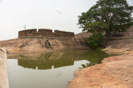 Dindigul, India - October 23, 2013: A short dam creates an artificial pond to collect rain water inside Dindigul Rock Fort. One lone tree and fortifications.