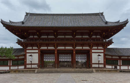 Nara, Japan - September 21, 2016: Large, wooden entrance gate to the Todai-ji Buddhist temple grounds. Leads to the inner courtyard in front of temple building. Gray roof, white walls, dark wood.