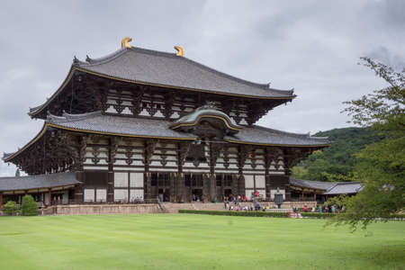 Nara, Japan - September 21, 2016: Side view of the tall wooden Todai-ji temple building which holds the largest statue of Buddha, called Daibatsu, in Japan. People in front, green lawn, gray sky. Editorial