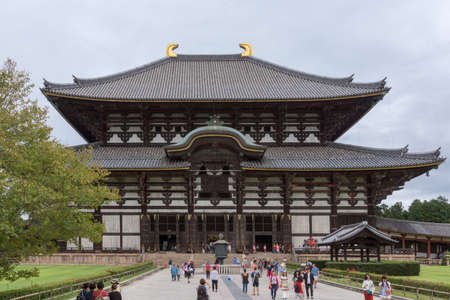 Nara, Japan - September 21, 2016: Front view of the tall wooden temple building of Todai-ji which holds the largest statue of Buddha, called Daibatsu, in Japan. People in front, walkway, gray sky. Editorial