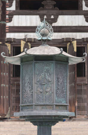 Nara, Japan - September 21, 2016: Focus on large bronze octagonal lantern in front of Todai-ji Buddhist Temple. Images of celestial musicians with the brown wood of temple building as  background. Editorial