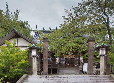 shinto: Kanazawa, Japan - September 22, 2016: Entrance to the historic Utasu Shinto Shrine downtown Kanazawa.Green foliage. Stairway. Guardian reading on his smartphone.