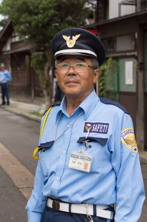 public safety: Kanazawa, Japan - September 22, 2016: Public officer is a security warden who directs traffic and parking in downtown Kanazawa. He is not a police officer but he keeps an eye on safety for all citizens in the neighborhood.