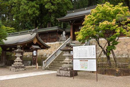 shinto: Takayama, Japan - September 23, 2016: Sakurayama Hachimon-go Shinto Shrine. Lions as guardians. Wood construction and green foliage. Sign and rinsing fountain. Editorial