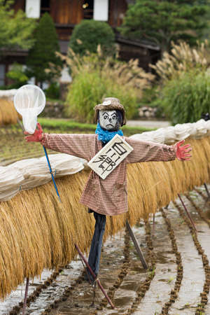 joined hands: Shirakawago, Japan - September 23, 2016: Closeup of well designed and decorated scarecrow with a neck sign and a butterfly net at Shirakawago. House with particular joined hands roof in the back.