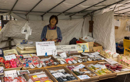 promotes: Takayama, Japan - September 24, 2016: Middle aged lady who is a vendor on the public morning market in front of the Jinya Hall promotes pickled and other merchandise. Combination of colors.
