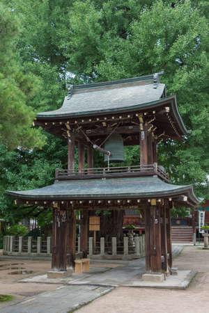 bell bronze bell: Takayama, Japan - September 24, 2016: Bell tower at Hikakokubun-ji Buddhist Temple has dark wood structure and bronze roofs under green trees.