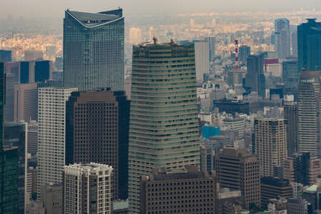 multitude: Tokyo, Japan - September 26, 2016: Aerial view since shot off Observatory tower. Close up of the Mori towers surrounded by a multitude of highrise buildings. Editorial