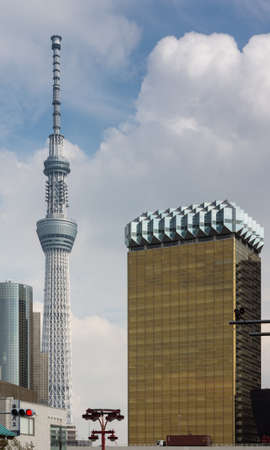 supposedly: Tokyo, Japan - September 26, 2016: Asahi Beer Company headquarters supposedly looks like a glass of lager beer, with tall Skytree tower in the distance under blue cloudy sky.