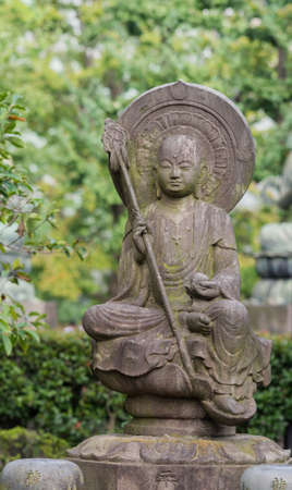 Tokyo, Japan - September 26, 2016: Closeup of stone statue of Bodhisattva sitting on lotus pedestal in garden at Senso-ji Buddhist Temple. Large halo. Holds staff and sphere. Green foliage.
