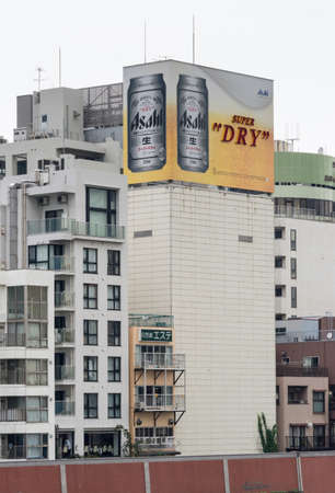 adds: Tokyo, Japan - September 28, 2016: An Asahi Super Dry lager beer can billboard on top of some older apartment buildings along the Sumida River. Mostly white buildings, gray sky. Beer Sign adds the color.