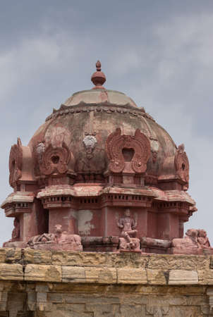 Dindigul, India - October 23, 2013: The Vimanam at the abandoned ruinous Shiva Temple on the Rock in Dindigul. Red painted dome features statue of sitting Shiva with foot on the dwarf, ignorance, and Nandi the bull. Editorial
