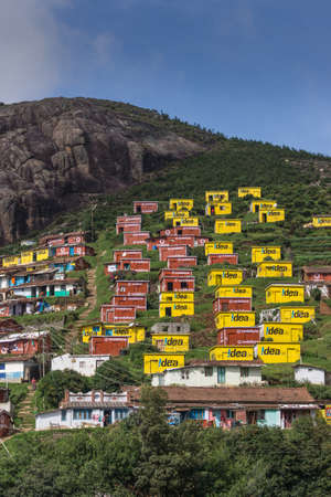 Ooty, India - October 25, 2013: Valparai village looks like a favela built on the slope of a hill. Bright yellow and wine red houses for poor people sponsored and painted by Idea and Vodaphone. Blue sky, rocky hill, green foliage, people.