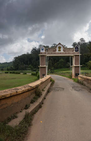 Madras: Ooty, India - October 25, 2013: Small rectangular side gate over narrow road into Wellington Cantonment. Features names and logos of garrison and college. Stormy sky, green foliage of forest in back. Hill and meadows.