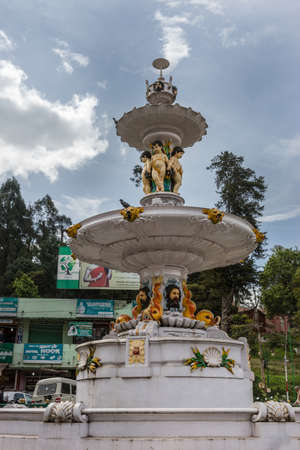 angels fountain: Nilgiri Hills, India - October 25, 2013: 19th century, non-flowing Adam Fountain on Charring Cross Square in Ooty. Shows three painted angels, adam faces, circular plateaus under light blue sky. City scape in back and green foliage.