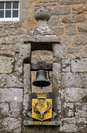 mindful: Cowdor, Scotland - June 2, 2012: The black bell hangs in gray stone niche above the golden coat of arms and slogan, Be Mindful. In the arch above the entrance gate to the courtyard of historic Cowdor Castle. Editorial