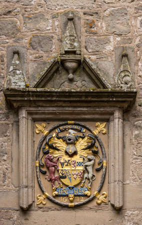 Cowdor, Scotland - June 2, 2012: Gold, red and blue coat of arms with slogan Be Mindful. Set in a wall of the courtyard of historic Cowdor Castle. Gray brown stone wall has date of 1638,
