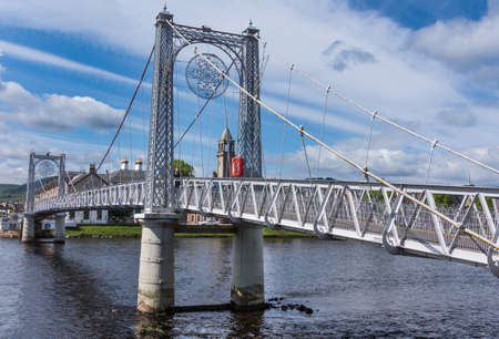 ness river: Inverness, Scotland - June 1, 2012: View along the pedestrian gray metallic Greig Street suspension bridge over Ness River.  Snowflake image. Blue sky with white clouds and houses.