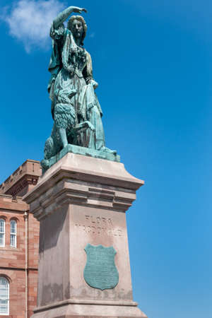 greenish blue: Inverness, Scotland - June 1, 2012: Greenish bronze Flora MacDonald statue shows the heroic lady and her dog against blue sky. Brown pedestal with bronze memorial plate. Part of castle in background. Stock Photo