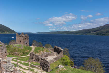 Loch Ness, Scotland - June 2, 2012: Shot of the wider deep blue Loch Ness with part of Urquhart Castle ruins in the foreground. Green surrounding hills. Light blue sky. Stock Photo