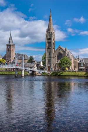 ness river: Inverness, Scotland - June 1, 2012: Combination photo of the Old High Church on the left and the Free Church of Scotland behind the Ness River with part of metallic Greig Street suspension bridge, under blue sky.