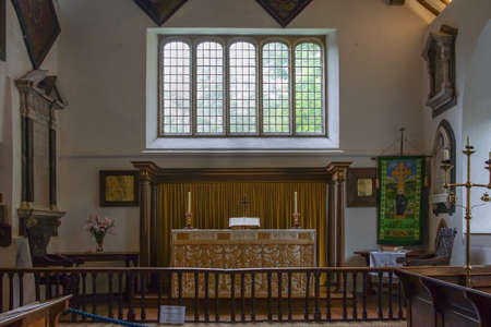 Grasmere, England - May 30, 2012: The chancel of the Saint Oswald Church is well lighted by a large window above the altar. Paintings and tablets decorate the walls. Candle and book on altar. Editorial