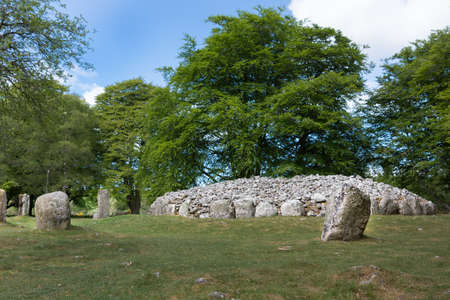 grave site: Inverness, Scotland - June 2, 2012: The menhir stone circle and grave site heap of gray stones at prehistoric Clava Cairns. Surrounded by green trees, grassy field and white clouds in blue sky. Stock Photo