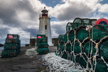 Lybster, Scotland - June 4, 2012: Green lobster traps are stacked on black stone pier of Lybster harbor with white lighthouse in back. White cords and red buoys. Dark clouds in blue sky.