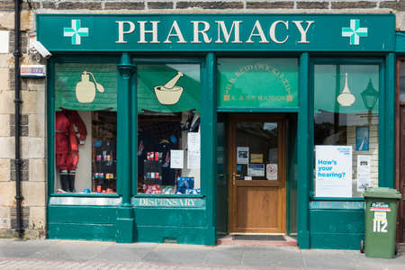 Wick, Scotland - June 4, 2012: Closeup of the green painted storefront of Wick Pharmacy owned by Mr. Manson. Display of colorful packages in windows. Trashcan upfront.