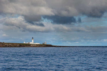 The white lighthouse complex on north end of Stroma Island on a rocky shore under heavy cloudy sky. Dark blue sea. Dominant color is blue but by a line of brown rocks. Stock Photo