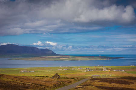 Look west. Mountain on Hoy Island. Flat Graemsay Island with white lighthouse. Green meadows and farms upfront. Atlantic blue ocean on horizon with inlet. Blue cloudy sky. Stock Photo