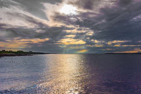 Seascape looking at entrance to silver to mauve Atlantic Ocean under dark cloudy evening sky wherein waning sun creates colorful lights. Stock Photo