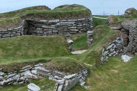 Skara Brae Neolithic Settlement. Group of ruins and fundaments of dwelling, set in the green dunes. Entrance to dwellings under ground. Gray and brown stones. Light blue Atlantic ocean in background.