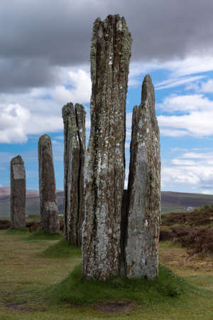 Ring of Brodgar Neolithic Stone Circle. Multiple gray menhirs with white and yellow mold spots stand erect on a grass field under blue and gray sky. Hills in the background.