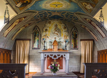 Orkneys, Scotland - June 5, 2012: Italian Chapel on Lamb Holm Island. Chancel and altar with bright, sharp and detailed wall and ceiling paintings featuring the madonna with child, angels and more Editorial