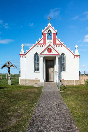 The entrance and front facade of the white and maroon painted Italian Chapel on Lamb Holm Island. Green lawn in front, against deep blue sky.