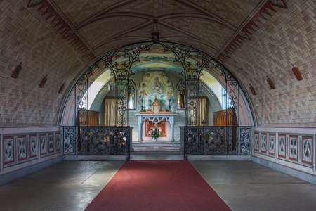 Orkneys, Scotland - June 5, 2012: The empty nave leads to the chancel with altar and wall paintings in Italian Chapel on Lamb Holm Island. Wine-red carpet, colorful reredos, natural light, domed ceiling.