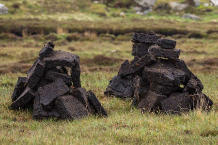 Closeup of two short stacks of blocks of black peat, the local fuel. Heaps on green-brown grassy field.