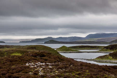 North Coast, Scotland - June 6, 2012: Irregularly shaped, gray-water Loch Eriboll under dark cloudy skies. Wide shot showing land tongues, background mountains and green and brown vegetation.