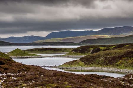 Irregularly shaped, gray-water Loch Eriboll under dark cloudy skies. Wide shot showing land tongues, background mountains and green and brown vegetation. Stock Photo